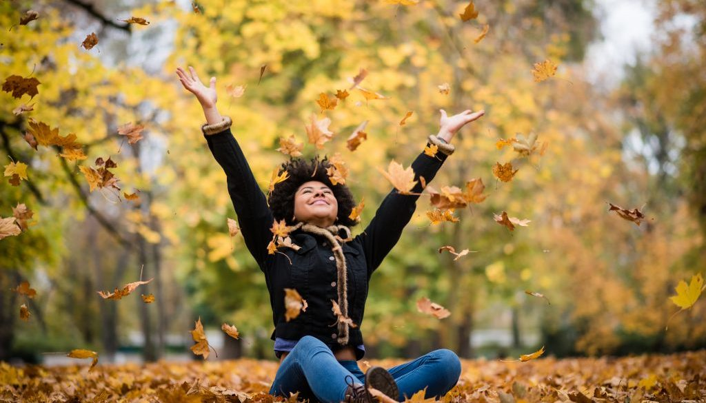 Joyous teen playing with dry maple leaves